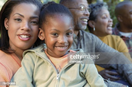 Portrait of mother and daughter with family in background : Stock Photo