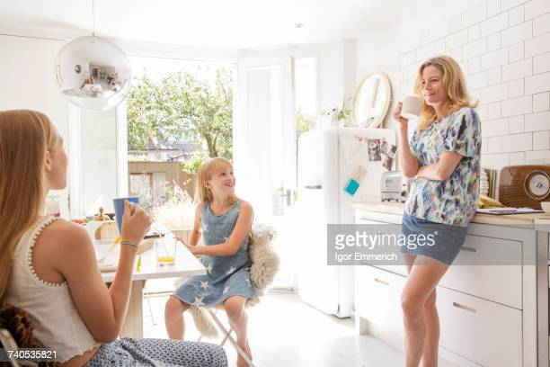 Portrait of mother and daughters in kitchen having breakfast together