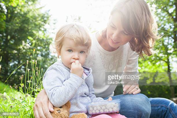 Portrait of mother and female toddler eating sweets in park