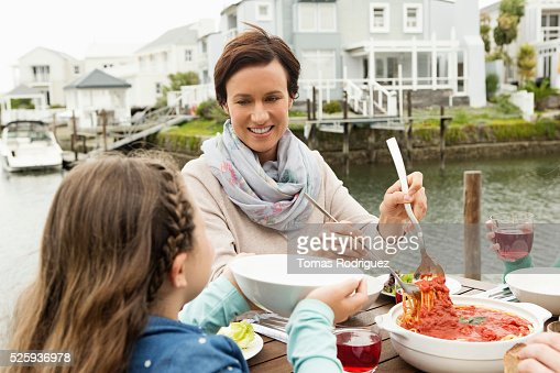 Portrait of mother and girl (6-7) eating outdoors : Stock Photo