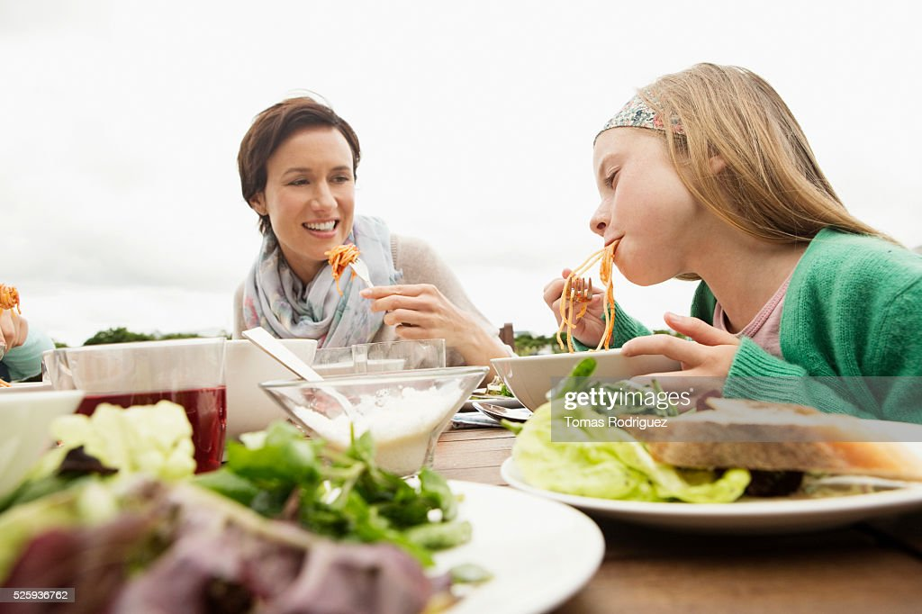 Portrait of mother and girl (8-9) eating spaghetti : Foto de stock