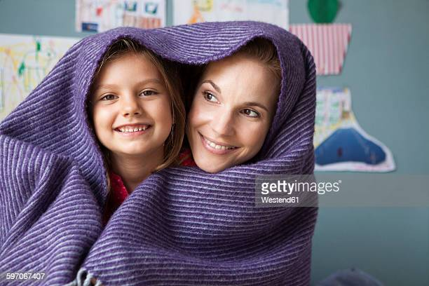Portrait of mother and little daughter with woollen blanket