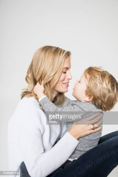 Portrait of mother and son against white background, face to face, smiling