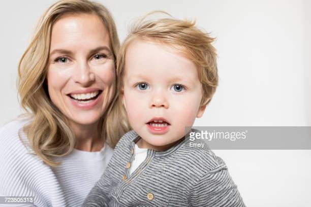 Portrait of mother and son against white background, smiling