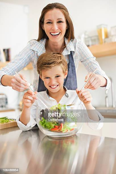 Portrait of mother and son (10-11) mixing vegetable salad in kitchen