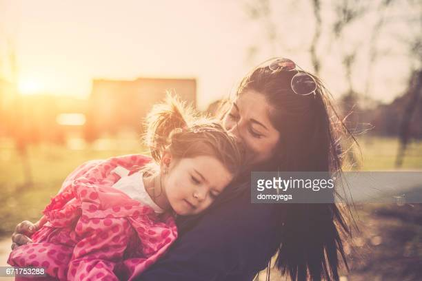 Portrait of mother embracing and kissing her little girl