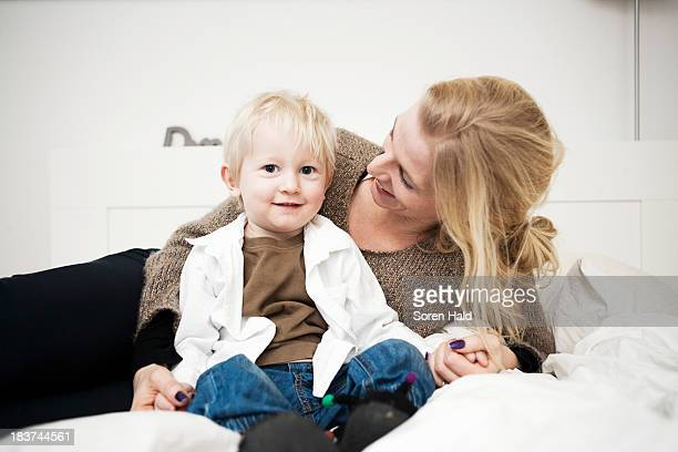 Portrait of mother holding hands with toddler son on bed