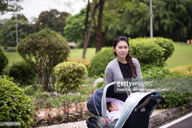 Portrait Of Mother Standing By Baby Stroller At Park