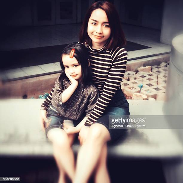 Portrait Of Mother With Daughter Sitting In Park