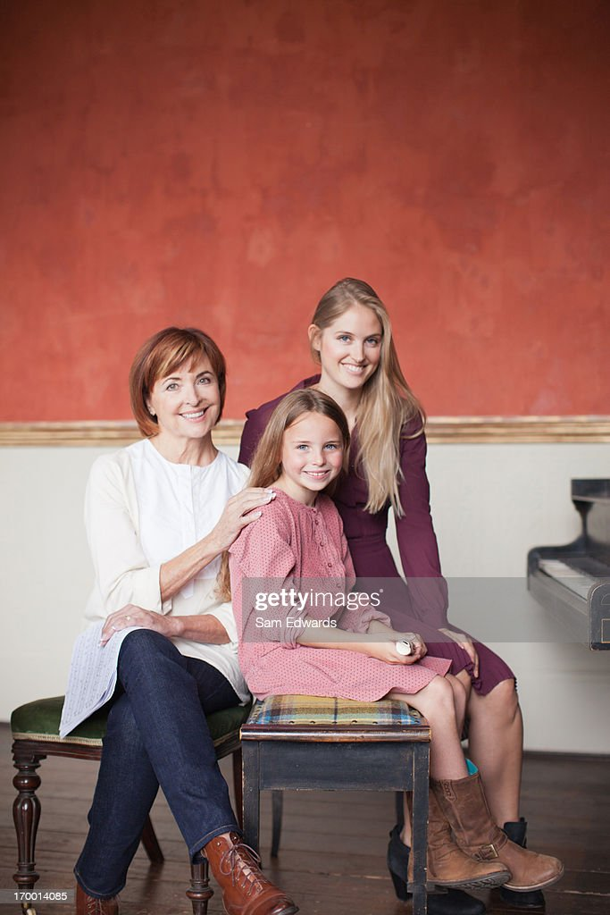 Portrait of multi-generation family sitting at piano : Stock Photo