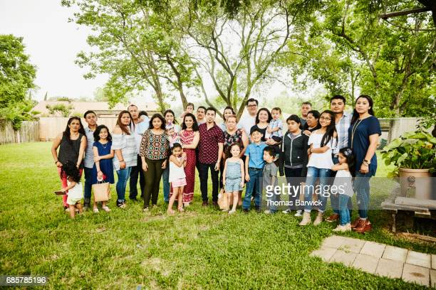 Portrait of multigenerational family gathered together for backyard birthday party
