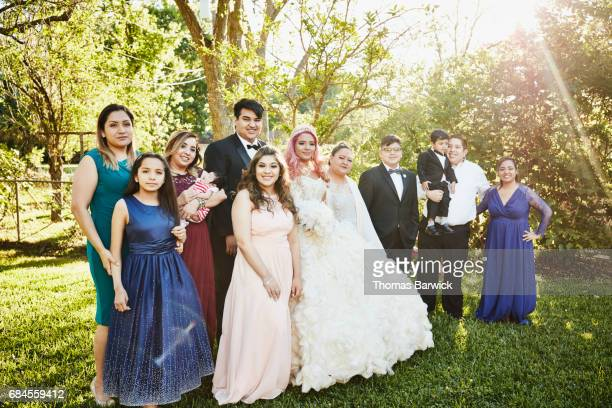 Portrait of multigenerational family standing in backyard with young woman dressed in quinceanera gown