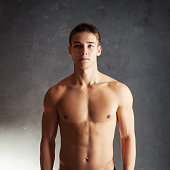 Portrait of muscular young man with naked torso against gray textured background