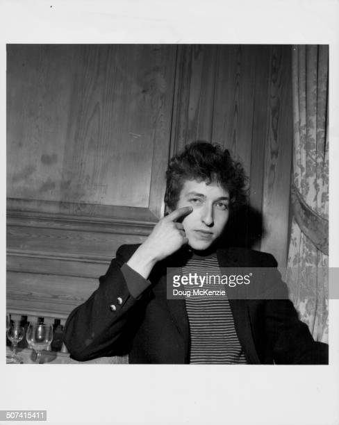 Portrait of musician Bob Dylan pointing to his eye April 1965