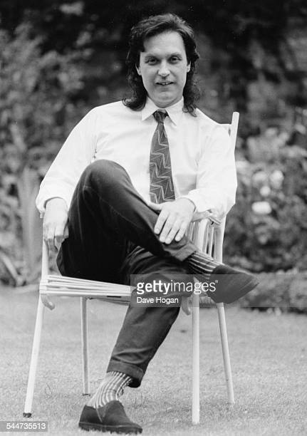 Portrait of musician Dave Davies sitting in a wicker chair outdoors September 24th 1984
