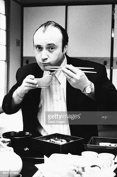 Portrait of musician Phil Collins eating a traditional Japanese meal with chopsticks while on tour in Japan circa 1988