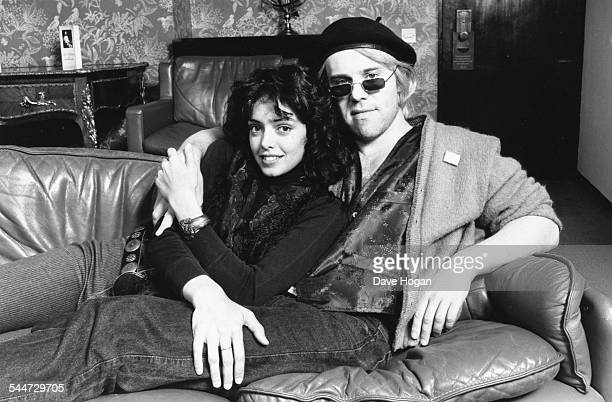 Portrait of musician Thomas Dolby and his girlfriend actress Kathleen Beller reclining on a couch together at the Town and Country Club in London...