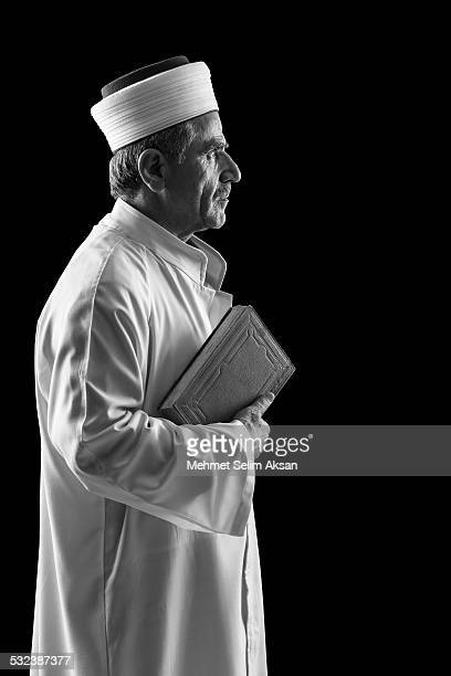 Portrait of muslim imam holding Koran