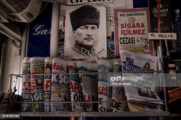 A portrait of Mustafa Kemal Ataturk the founding figure of modern Turkey is seen above newspapers at a news media kiosk in the upper class...