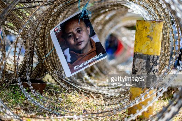 A portrait of Myanmar's ultranationalist Buddhist monk Wirathu is attached to barbed wire in front of the Myanmar embassy in Jakarta on September 8...