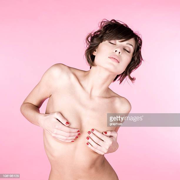 Portrait of Naked Young Woman Covering Breasts with Hands