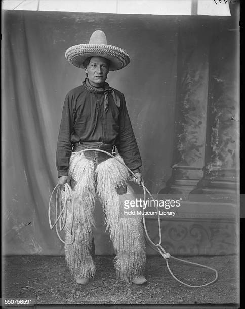 Portrait of Native American Oglala Sioux Ivan Star Comes Out wearing cowboy clothing sheepskin chaps tall cowboy hat and carrying a lariat at the...
