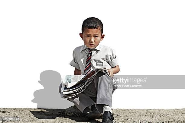 portrait of Nepali school boy holding a newspaper
