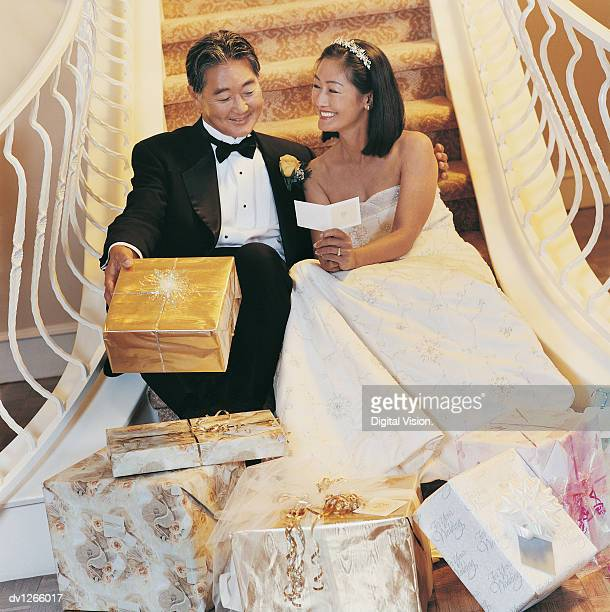 Portrait of Newlyweds Sitting on Stairs With Presents