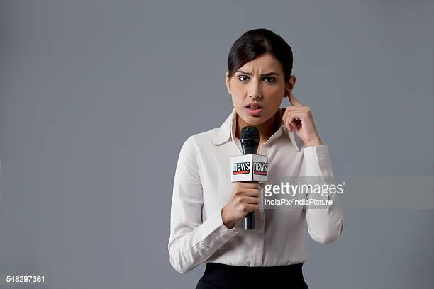 Portrait of news reporter listening against colored background