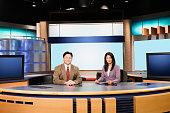 Portrait of news team sitting behind desk in newsroom