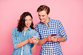 Portrait of nice lovely attractive cheerful cheery couple holding in hands devices chatting isolated over pink pastel background