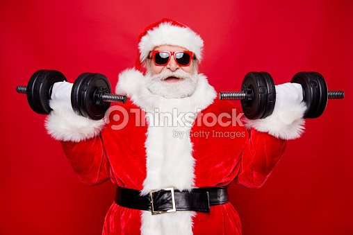 Portrait of nice optimistic positive modern stylish strong sporty muscular virile Saint Nicholas in gloves fur white red winter clothes holding lifting two big dumbbells isolated over red background : Stock Photo