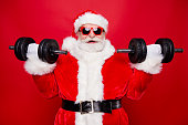 Portrait of nice optimistic positive modern stylish strong sporty muscular virile Saint Nicholas in gloves fur white red winter clothes holding lifting two big dumbbells isolated over red background