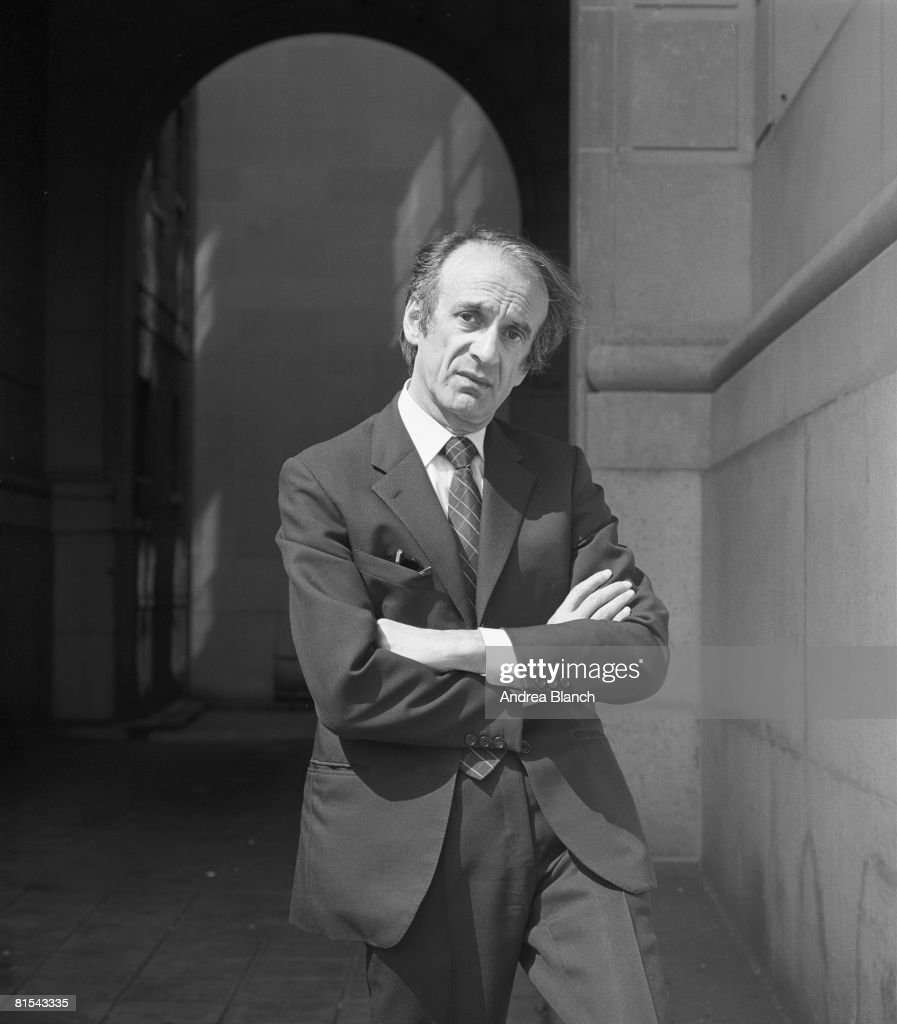 Portrait of Nobel Prize-winning author and Holocaust survivor Elie Wiesel, as he poses in a suit with arms folded, 1983.