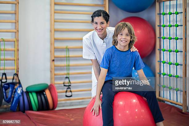 Portrait of nurse and child doing rehabilitation