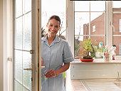 Portrait of nurse entering front door of patients house