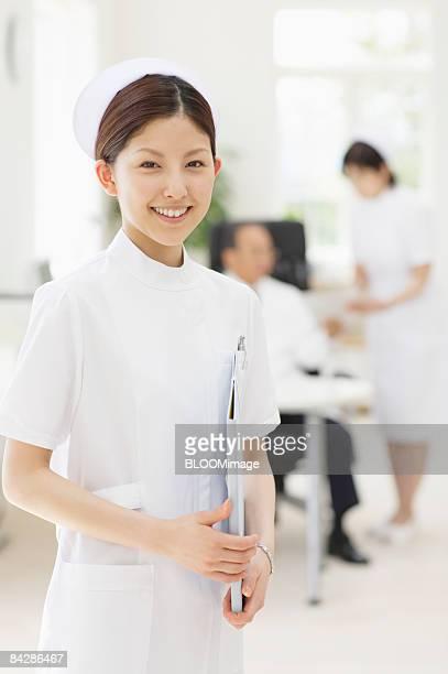 Portrait of nurse holding file folder, smiling