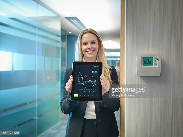 Portrait of office worker holding digital tablet next to office thermostat adjusted to make energy savings