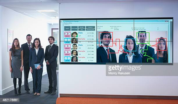Portrait of office workers standing next to face recognition software system