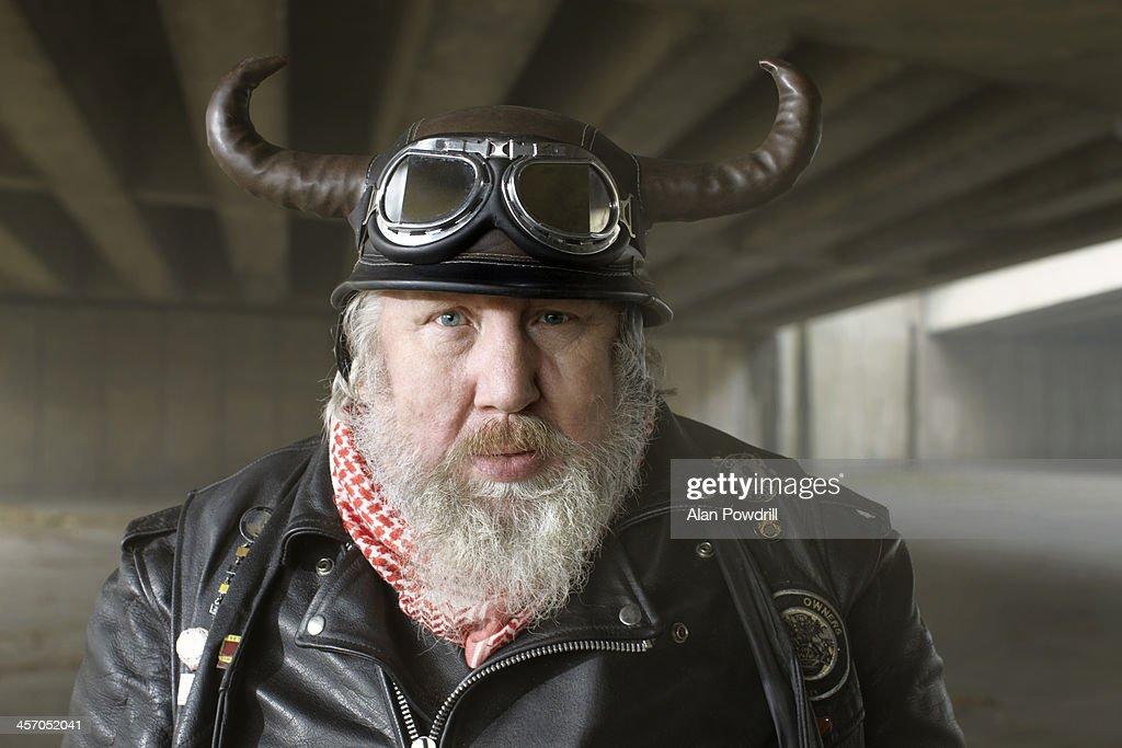 Portrait of old biker with horn helmet