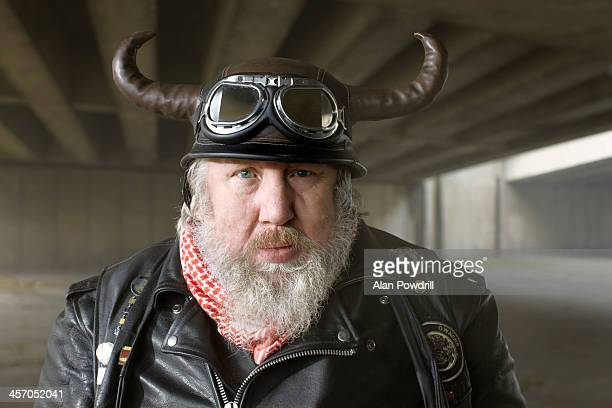 Portrait of old biker with horn helmet