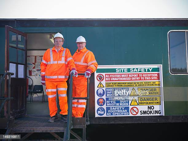 Portrait of opencast colaminers standing next to Health and Safety sign