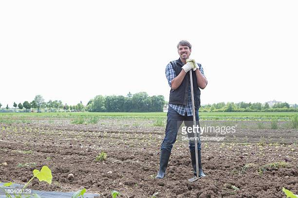 Portrait of organic farmer with rake