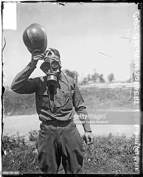Portrait of Oscar M Solbert a captain wearing a gas mask and tipping his metal helmet to the camera standing in a field at a camp 1910s This image...