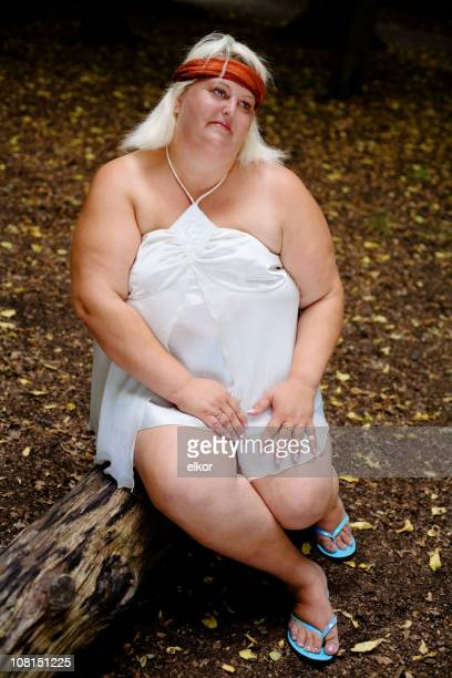 Portrait of Overweight Woman Sitting on Log in Forest