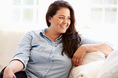 Portrait Of Overweight Woman Sitting On Sofa Looking Away From Camera Smiling