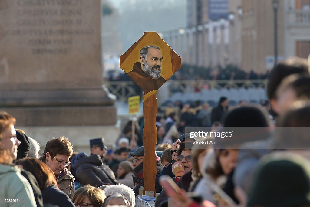 A portrait of Padre Pio is seen in the crowd as faithfull gather in St Peter's square before the arrival of Pope Francis for an audience to the Padre Pio Prayer Groups, on February 6, 2016 in Vatican. Pio was revered during his lifetime (1887-1968) and his popularity has continued to grow since his death, particularly in Italy, where mini-statues and pictures of the mystical Capuchin friar are ubiquitous. / AFP / TIZIANA FABI