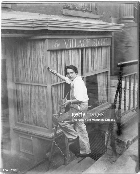 Portrait of painter Charlotte Powell in overalls and short hair painting the outside window of The Village Store Greenwich Village New York New York...