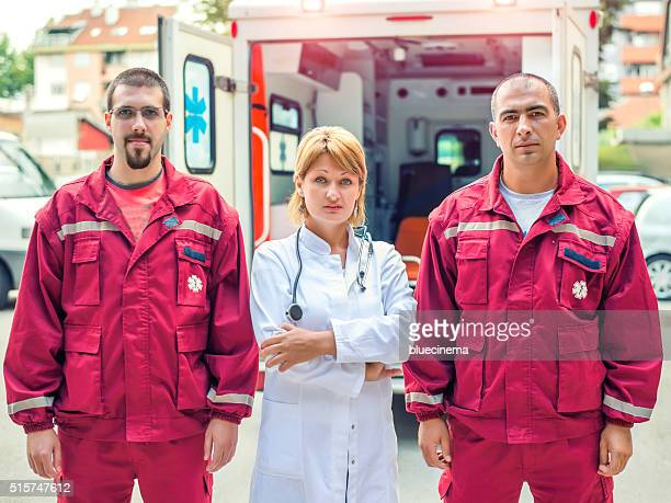 Retrato de técnico en urgencias médicas trabajadores en frente de una ambulancia