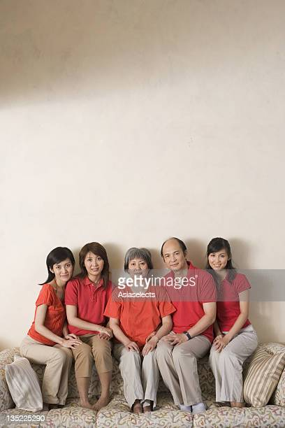 Portrait of parent and their three daughters sitting on a couch